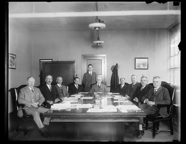 Brains of Aeronautic World represented on National Advisory Committee for Aeronautics. The National Advisory Committee for Aeronautics is photographed in Washington the other day when they met at the Navy Department. The duties of the Committee, as provided by Congress, are to supervise and direct the scientific study of the problems of flight, with a view to their practical solution. In the photograph, left to right: G.W. Lewis; Charles G. Abbet, Secretary of the Smithsonian Institution; Orville Wright, Inventor of the airplane; Commander John H. Towers; U.S.N., here of the first trans-atlantic flight in 1919; Joseph S. Amos, Chairman; Brig. Gen. Benjamin D. Foulois, first U.S. Army Aviator; William P. MacCracken, former Secretary of Commerce for Aviation; Charles F. Marvin, Chief U.S. Weather Bureau; David W. Taylor, Vice Chairman. Standing is John F. Victory, Secretary