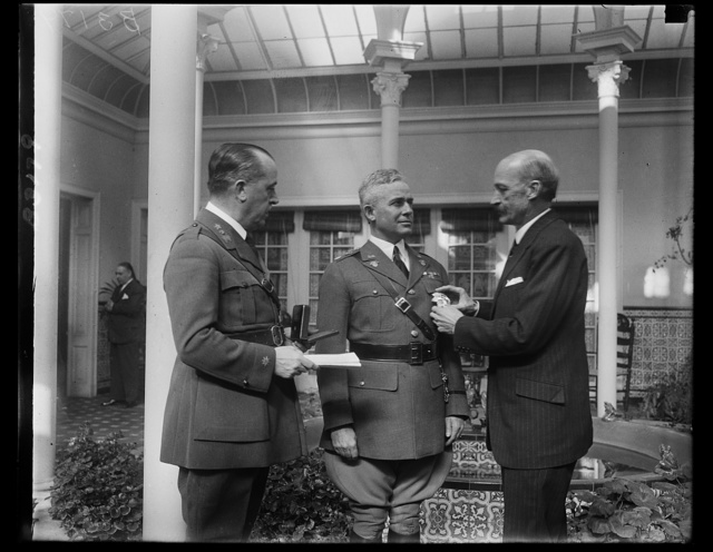 Commandment of West Point Cadets is decorated by Spanish Ambassador to U.S. Lieut. Col. Campbell B. Hodges, Commandment of Cadets at West Point, being decorated with the Spanish Military Cross of Merit by Ambassador Padilla today. Col. Hodges received the decoration for his service at the American Embassy in Spain from 1923 to 1926. In the photograph, left to right; Maj. Victoriane Casjaris, military attache of the Spanish Embassy; Col. Hodges; and Ambassador Padilla