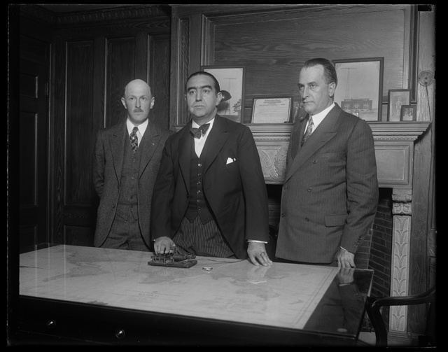Direct Radio Telegraphic communication between the United States and Spain was officially opened at the offices of the R.C.A. Communications in Washington this morning. Mariano de Amoedo, charge d'affaires of the Spanish Embassy is shown pressing the telegraphic key opening the service. The King of Spain and the Prime Minister were at the other end of the circuit. In the group, on the left is F.P. Guthrie of the Radio Corporation and on the right, David A. Salmon, Chief of the Bureau of Indexes and Archives, Dept. of State