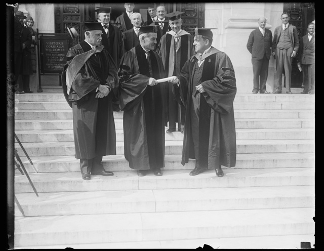 Great Britain's Prime Minister receives degree from George Washington University. Ramsey MacDonald, Prime Minister of Great Britain, receiving an honorary degree of Doctor of Laws from President Cloyd Hock Martin (right) of George Washington University in the National Capital. The British Ambassador Sir Esme Howard is on left