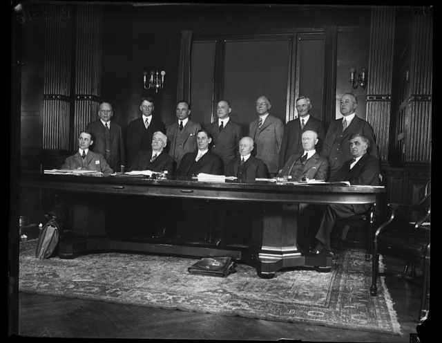 [Group; includes, in front row, Ray Wilbur, third from left, and Charles Adams, foruth from left]