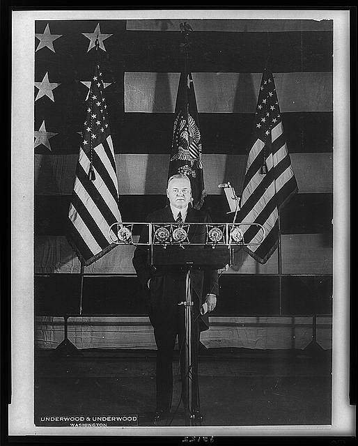 [Herbert Hoover, full-length portrait, standing, facing front, in front of microphones and three flags]