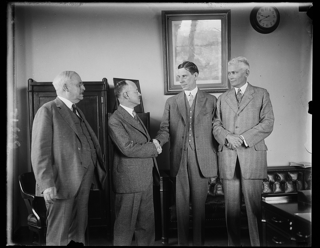 New U.S. Commissioner of Pensions assumes post at Interior Department. The new Commissioner of Pensions of the Department of Interior, Earl D. Church of Hartford, Conn. received a hearty greeting from Secretary of the Interior Ray Lyman Wilbur, as he assumed his new post today. In the photograph, left to right: Rep. E.H. Fenn of Connecticut; Commissioner E.D. Church; Secretary Wilbur; and Senator Hiram Bingham of Connecticut
