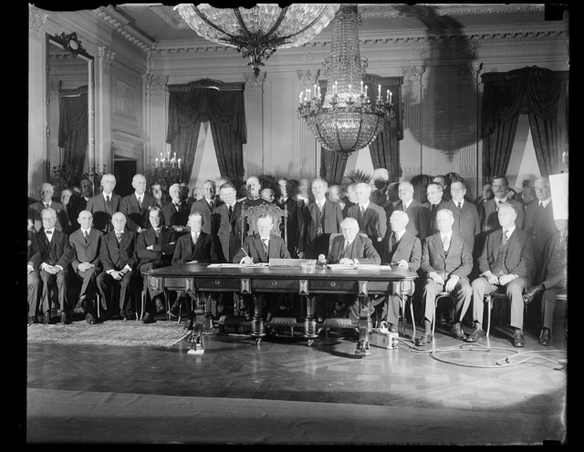 President Coolidge signs Kellogg Treaty. President Coolidge today formally signed the document of ratification of the Kellogg treaty before a distinguished gathering in the east room of the White House, including Vice President Dawes, members of the Cabinet and members of the Senate and House. In the front row, left to right: Vice President Dawes; President Coolidge; Secretary of State Frank B. Kellogg; Secretary of the Treasury Mellon; and Secretary of War Davis. in the back row, left to right: Senator William E. Borah; Senator Claude A. Swanson; Senator Thomas F. Walsh; Vice President-elect Charles Curtis; and Senator D.O. Hastings