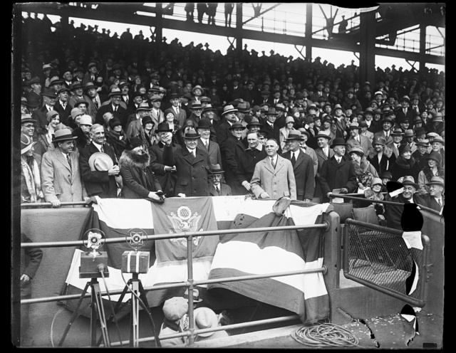 President Hoover officially opens baseball season in National Capital. President Hoover tossing out the first ball to officially open the baseball season in Washington today. The Washington Senators played in the Philadelelphia Athletics in the season's opener. In the photograph, left to right: Secretary of Agriculture Arthur M. Hyde; Mrs. Herbert Hoover; President Hoover; Secretary of Treasury Andrew Mellon (sitting) Secretary of War James W. Good; Walter Johnson; and Clark Griffith