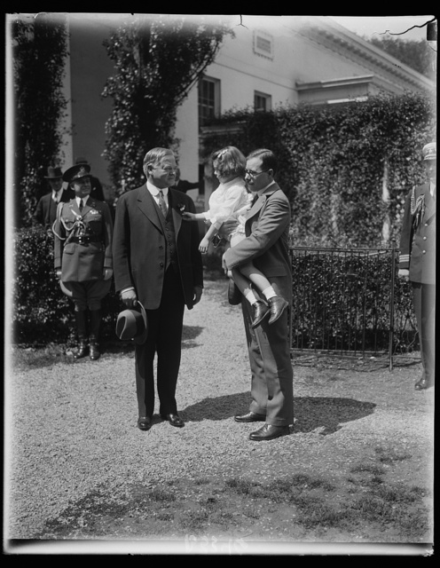 "President Hoover receives first ""Buddy Poppy"". Eugene S. Carver, Commander-in-chief, Veterans of Foreign Wars, holds little Betty Boyer of Washington, while she pins the first ""buddy poppy."" The poppies are sold every year at this time for the benefit of American Veterans of Foreign Wars"