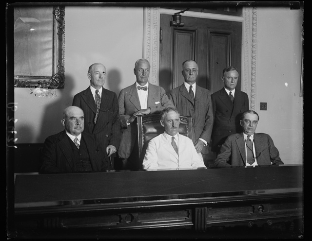 Reparations Committee confer with Secretary of State Stimson. Members of the American Reparations Commission, who recently returned to this country after negotiating a settlement with the European nations, were in conference with the Secretary of State Henry L. Stimson today. In the front row, seated, left to right: J. Pierpont Morgan; Secretary Stimson; and Owen D. Young, chairman. In the back row, left to right: Thomas W. Lamont; Thomas Nelson Perkins; Undersecretary of State Joseph P. Cotton; and Assistant Secretary of State William R. Castle