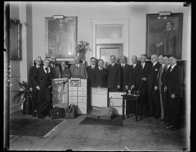 Secretary of Agriculture is surprised with gifts from members of personal staff when he was Governor of Missouri. Led by members of his personal staff when he was Governor of Missouri and fellow Missourians, Secretary of Agriculture Arthur M.Hyde, was given a surprise party at his office in Washington today. They presented him with a complete traveling outfit and in short speeches each one paid a glowing tribute for Missouri's friendship for him. In the center of photograph, left to right: Dwight F. Davis, former Secretary of War; Secretary Hyde; and Col. M.F. Natter of Kansas City and member of Secretary Hyde's staff when he was Governor