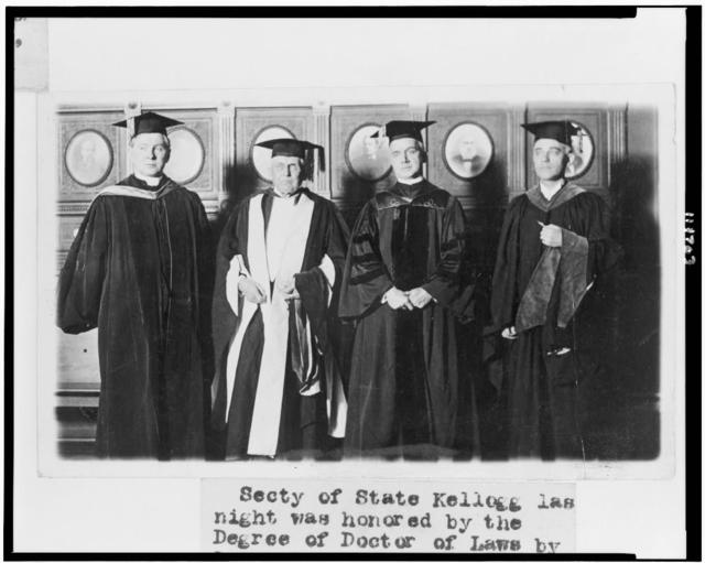 [Secretary of State Frank Kellogg, in cap and gown, being honored with the Degree of Doctor of Laws, by Georgetown University, standing with three other men]