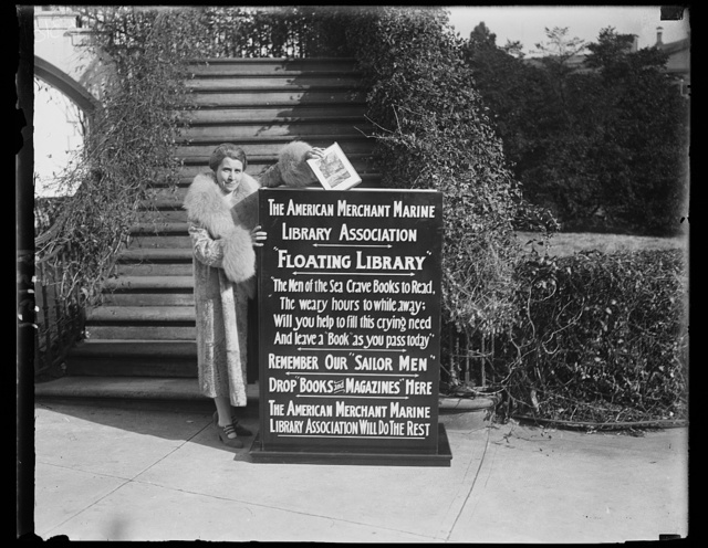 """Stars the drive for books. Mrs. Coolidge dropped the first book into the big box that starts the drive by The American Merchant Marine Library Association for a """"floating library"""" for our """"sailor men"""""""
