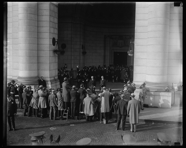 """The battery of cameras. Here is the way the cameraman greeted Premier MacDonald at the Union Station, Washington, today upon his arrival to confer with President Hoover. This shot was made as the battery was """"shooting"""" the Premier with Secretary of State Stimson"""