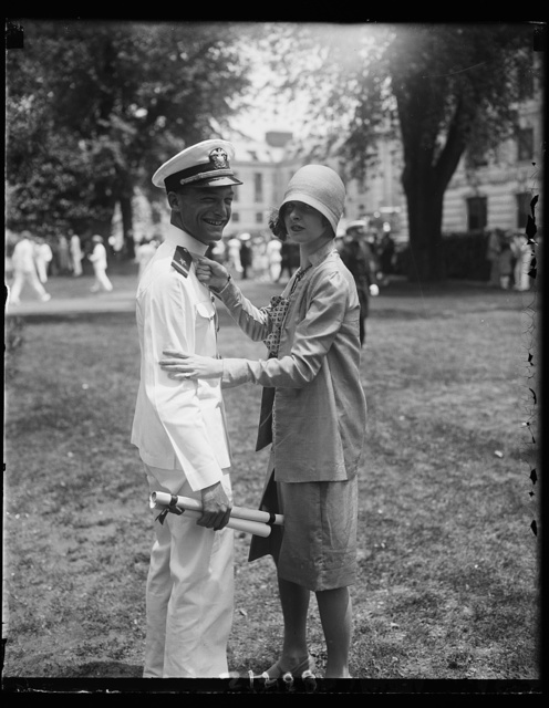 Washington girl pins epaulettes on sweetheart graduate at U.S. Naval Academy., A.C. Walker of Asheville, North Carolina, member of the graduating class of Annapolis today, has the epaulettes of ensign in the United States Navy