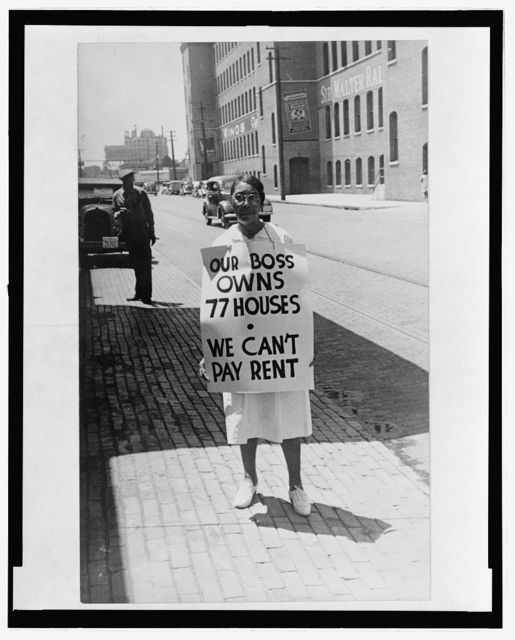 "[African American(?) woman standing on a street holding a sign reading ""Our boss owns 77 houses,  we can't pay rent]"
