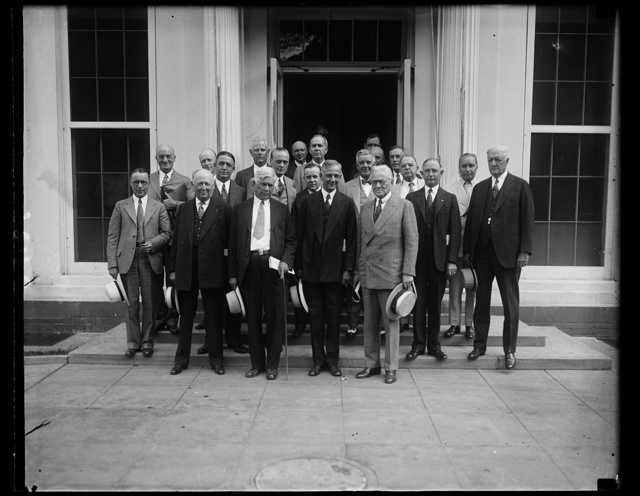 Bankers and drought relief plans. Twelve drought-stricken states sent representatives, most of them well known bankers, to confer with President Hoover and his relief committee to discuss plans for extending financial aid to farmers. Secretary of Agriculture Hyde is in the center of the photograph. Others are: Clyde Henedricks, Alabama; J.H. Stanley, Arkansas; Elmer Stout, Indiana; Melvin A. Traylor, Illinois; Byron A. Limbecker, Kansas; Nicholas Desker, Kentucky; Dr. D. Hoss, Virginia; Morton Frentis, Maryland; Arnold G. Stifel, Missouri; Edward A. Seiter, Tennessee; F.H. Fugus, Texas; Fred A. Scott. Virginia; F.D. Drumholler, West Virginia; Charles Reiman, Federal Reserve Bank; Hugh S. Mackey, manager, International Credit Bank; and members of the President's drought relief committee [White House, Washington, D.C.]