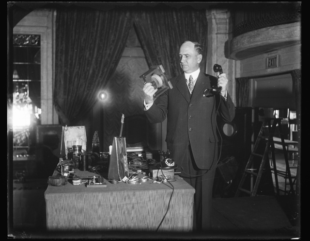 Demonstrates Bell Laboratory wonders. Sergius P. Grace, Vice-President of the Bell Telephone Laboratories, shows the old and the new in telephones. That in his right hand is a model of Alexander Graham Bell's first telephone through which sounds were first electronically transmitted in 1875. The larger apparatus near his right hand is the artificial lung and larynx, which enables people with paralyzed vocal cords to talk again. 12/30