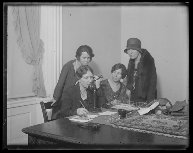 Feminists telephone the Hague to determine their status in proposed World Code. The National Woman's Party in Washington was all agog today as Mrs. Harvey W. Wiley telephoned Miss Doris Stevens, chairman of the InterAmerican Commission of Women at the Haugue, to ascertain whether the World Code now being drawn up by the Codification Conference of International Law will be based on sex discrimination. In the photograph, left to right: Miss Anita Pollitzer of South Carolina; Mrs. Harvey W. Wiley; Miss Alice Paul; and Miss Elsie Hill of Connecticut