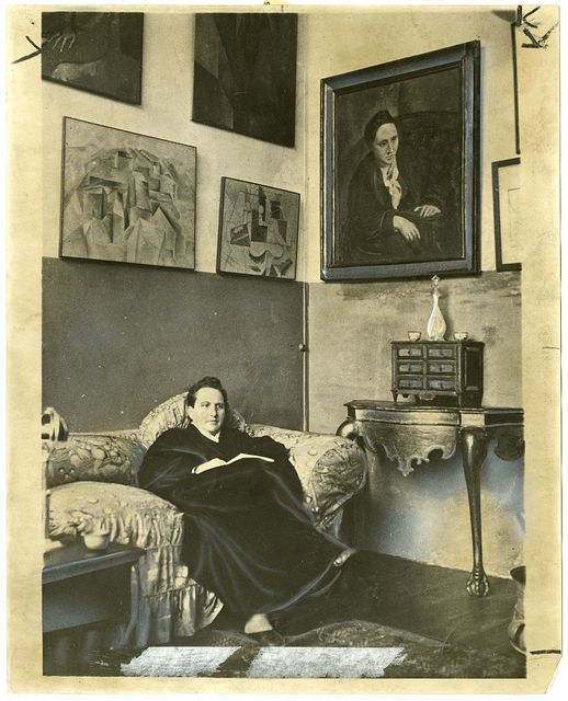 [Gertrude Stein sitting on a sofa in her Paris studio, with a portrait of her by Pablo Picasso, and other modern art paintings hanging on the wall behind her]