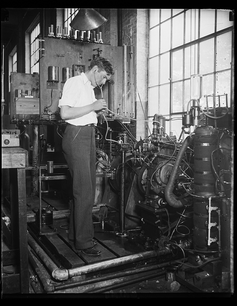 """Government expert listens to broadcasts of automobile [...] The Automotive Section of the Bureau of Standards is studying the anti-knock proportion of fuel used in automobile and aircraft engines and the scientist in this photograph is """"listening in"""" to the signals of an engine instead of listening to a radio broadcasting station. Eventually, these studies may evolve a new engine, one that will use fuel more economically and efficiently"""