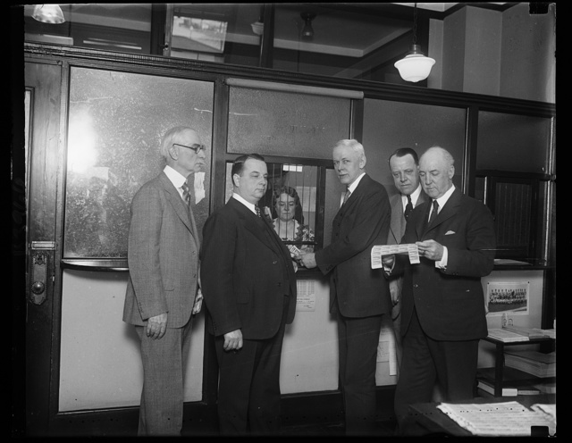 Graf Zeppelin stamps go? Assistant Postmaster General Frederic A. Tilton purchasing the first Graf Zeppelin stamps which were sold at the Washington city post office today. Mrs. M.C. Shaughnessy, Assistant Philatolic Agent, is shown selling the stamps to the General. Others in the photograph, left to right: Assistant Washington Postmaster W.H. Haycock; Philip H. Ward, editor, Makeel's Weekly Stamp News; Assistant Postmaster General Tilton; L. Eidsness, superintendent, Division of Stamps; and William M. Mooney, Washington Postmaster
