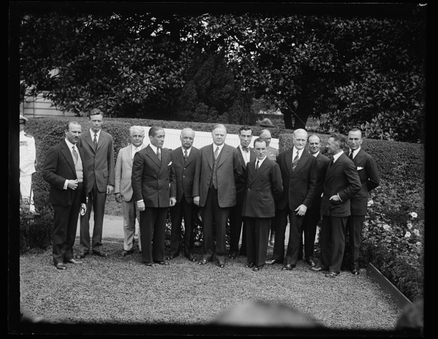 [Group, left to right: unidentified, Charles Lindbergh, James J. Davis, unidentified, Charles Curtis, Herbert Hoover; John Pershing, 4th from right]