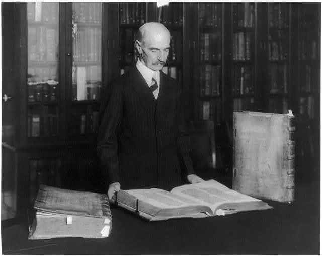 [Herbert Putnam, half-length portrait, standing, facing right, with the three volume Gutenberg Bible, Library of Congress]