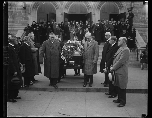 "Labor leaders attend Mother Jones funeral. Men high in the ranks of labor circles took part in the last rites for ""Mother"" Jones, 100 year-old labor crusader. Standing in the middle of the group of three at the right is William N. Doak, newly appointed Secretary of Labor. The casket is being borne from St. Gabriel's Catholic Church in Washington, where services were held, after which the body was sent to Mount Olivet, Ill., to be buried beside five of her ""boys"" slain there years ago in one of the many labor wars in which she participated. This was one of the last requests of the militant laborite, whose full name was Mrs. Mary Harris Jones but who was known simply as ""Mother"" by her thousands of ""boys"" throughout the country. 12/3/30"
