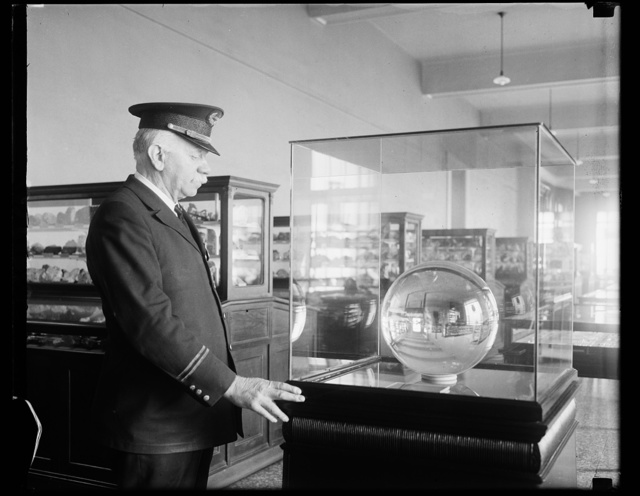 Largest perfect sphere of crystal in world now in National Museum. The National Museum in Washington has been presented with a perfect sphere of flawless crystal, believed to be the largest in the world. It is 12 and seve and seven eighths inches in diameter and weighs 106 pounds. Captain George Johnson, of the museum guards, is shown in photograph