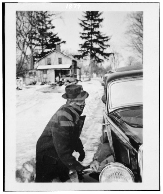[Leadbelly, three-quarter-length, profile, facing right, lifting car out of snow, at the home of Mary Elizabeth Barnicle, Wilton, Conn.]