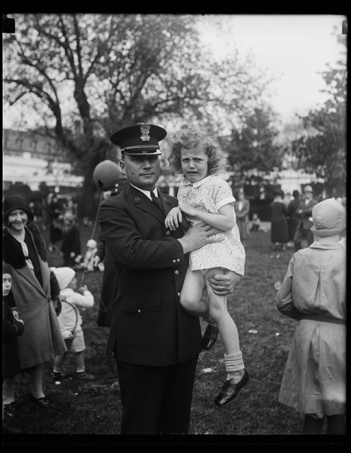 """Lost in action."" Little Gloria Largent was the first youngster to stray away from her parents on the White House lawn today where thousands of Washington children rolled their Easter eggs today. White House officer B.B. Bradley is holding Gloria"