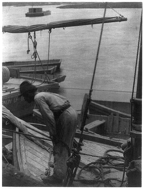 [Man standing in bow of fishing boat]