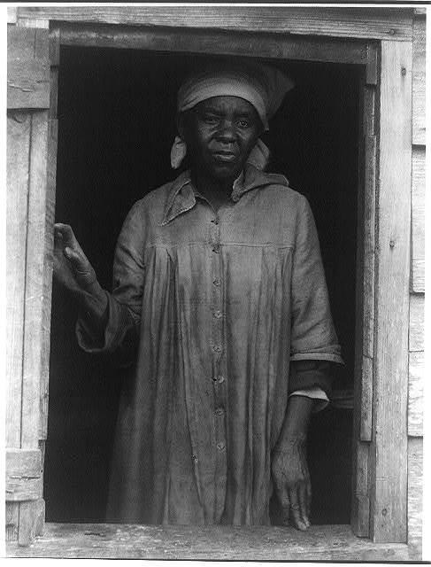 [Negro woman standing in window]