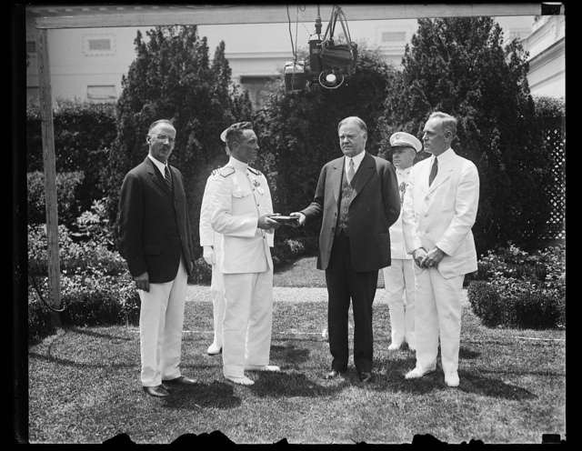 President Hoover presents special gold medal to Admiral Byrd. Rear Admiral Richard E. Byrd receiving from President Hoover the special gold of the National Geographic Society at the White House today. In the photograph, left to right; Gilbert Grosvener, President of the National Geographic Society; Admiral Byrd; President Hoover; and Ernest Lee Jahnke, Assistant Secretary of the Navy
