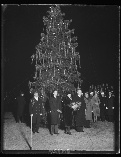 "President lights Christmas tree. President Hoover pressed the button which lighted Washington's community Christmas tree just before he began his brief ""Merry Christmas"" radio address to Americans from coast to coast. Mrs. Hoover accompanied the President to the impressive Christmas program, which included music by the U.S. Marine band. 12/24/30"