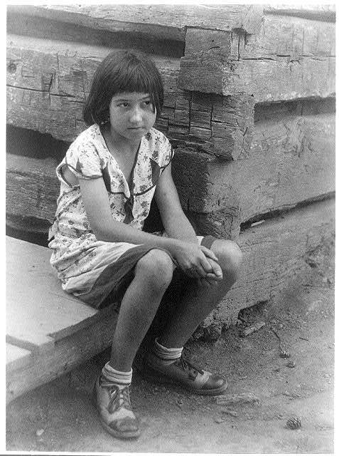 [Small girl seated by log cabin, no. 1]