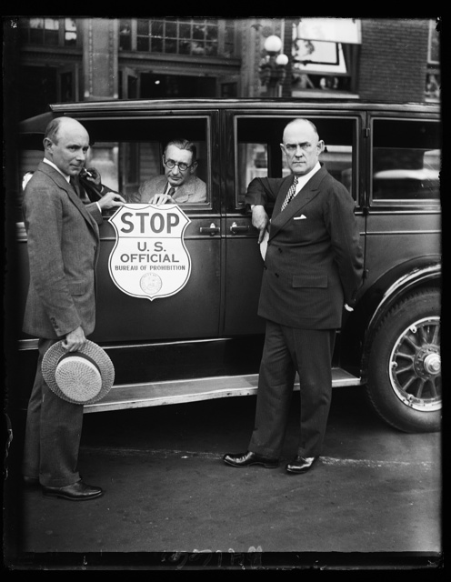 Stop when you see this sign. This is the new insignia plate the Bureau of Prohibition has adopted for use by prohibition agents in stopping suspected automobiles. In the photograph, from left to right, are; Prohibition Administrator Ames Woodcock, H.M. Lucious, secretary of the Automobile Club of Maryland, and Ernest M.Smith, vice- president of the A.A.A.