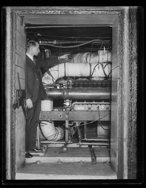Tests motors by synthetic cold. C.D. Bruce, of the automotive power plant section of the Bureau of Standards, makes a test of airplane motors to show how much coldness they can stand due to high altitude. The testing pipes get as cold as 53 degrees below zero. 12/30/30