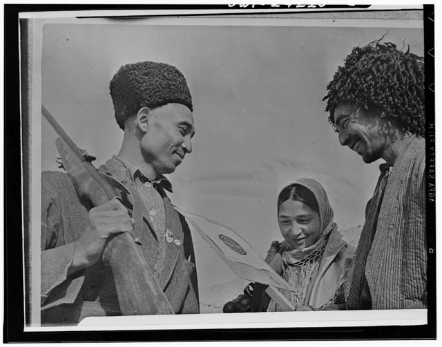 Turkmenian farm woman who is a member of a shooting circle, checking her score with other members in the USSR (Union of Soviet Socialist Republics)