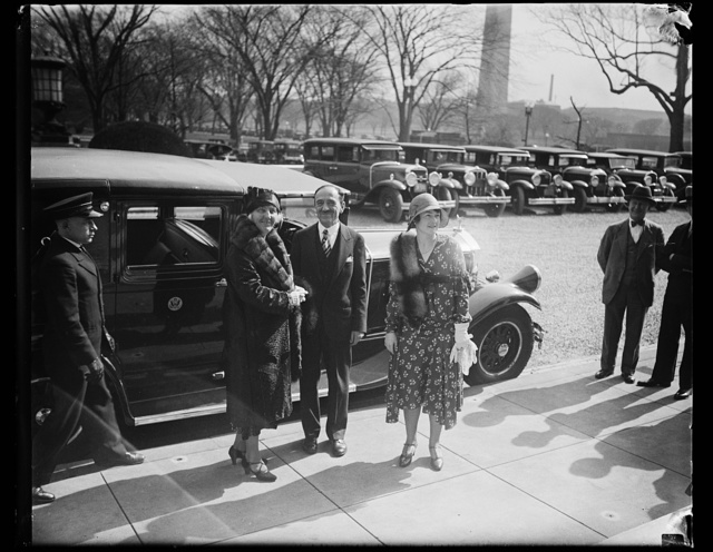 [Unidentified people next to automobile; Washington Monument in background]