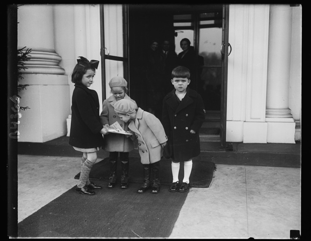 White House children receive greetings. Peggy Ann and Herbert Hoover, 3rd, received a message of Christmas greetings from the children of Washington. Kitty Murray and Harry G. Holme, Jr., both 6 years old, called at the White House and presented the message to the President's grandchildren. Left to right: Kitty, Peggy Ann, Herbert, and Harry. 12/24/30