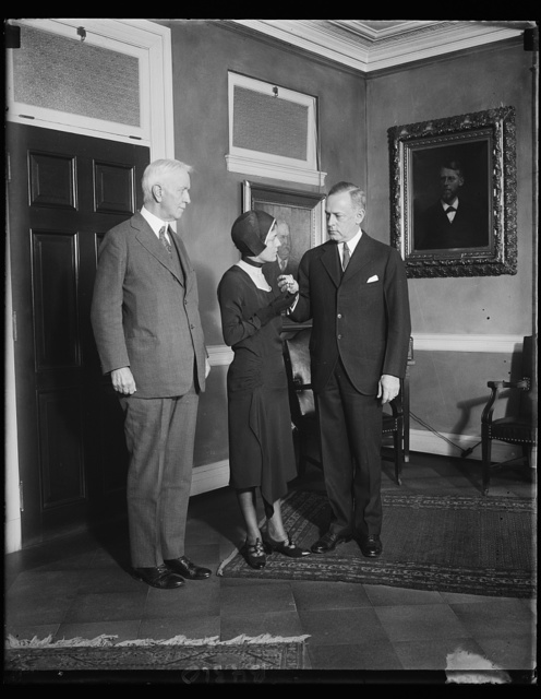 """Widow of noted flyer receive medal. 12/13/30, Mrs. Florence Shaw Page receives the Distinguished Flying Cross awarded posthumously to the late Capt. Arthur H. Page, U.S. Marines, for this """"pioneering"""" scientific [...] and successful accomplishment in the art of blind flying."""" The particular flight for which he received the medal was from Omaha to Anacostia, D.C., the distance of 1,000 miles having been made by flying blind the entire distance in one day. Capt. Page was also noted for having won the Curtiss Marine Trophy Race last spring, flying the 100-mile course at an average of 164 miles an hour. He died from injuries received when his plane crashed during the Thompson Trophy Race at Chicago last September. In the photograph, left to right: Maj. Gen. Ben H. Fuller, Commandant of the Marine Corps.; Mrs. Page and Ernest Lee Jahncke, Assistant Secretary of the Navy"""