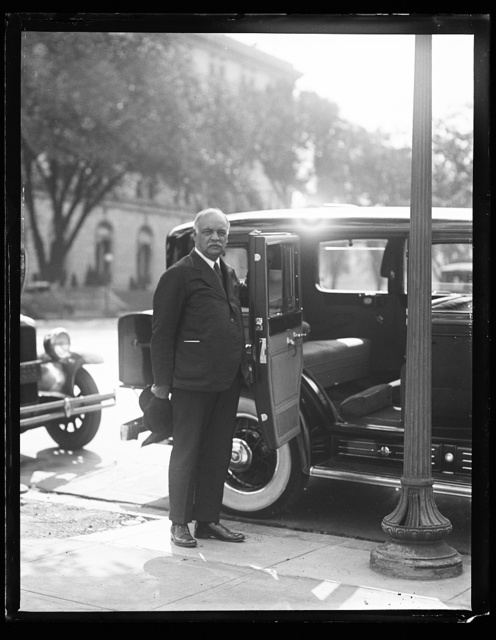 [Charles Curtis next to automobile]