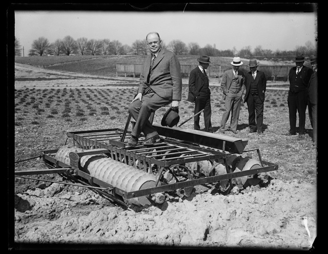 [Man in suit on farm machinery]