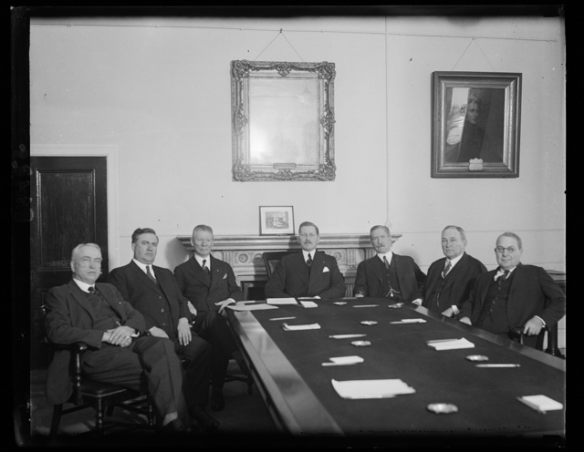 Meeting of commission to study methods of removing profits from war. The commission, recently created by Congress, to study methods fro removing profits from war, and for effecting an equitable distribution of the burdens of war, held its first meeting today in the office of the Secretary of War, Patrick J. Hurley. Secretary Hurley was elected chairman; Senator Davis A. Reed, Vice Chairman; and Rep. Lindley H.Hadley, Secretary. In the photograph, left to right: Rep. John J. McSwain, South Carolina; Rep. William P. Holaday, Illinois; Rep. Lindley H. Hadley, Washington; Secretary of War, Patrick J. Hurley; Senator Claude A. Swanson, Virginia; Senator Joseph T. Robinson, Arkansas; and Rep. Ross A. Collins, Mississippi