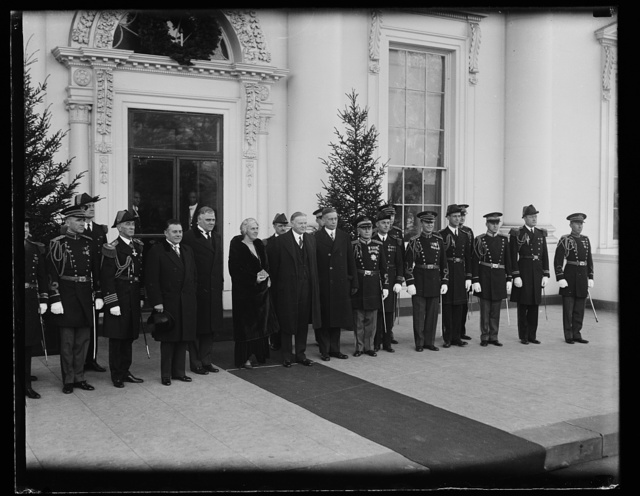 Presidential group at reception. The president and Mrs. Hoover photographed with the White House secretaries and military and naval aides, at the New Years reception. In the center of the group, left to right: Secretaries Lawrence Richey and George Akerson, President and Mrs. Hoover and Walter Newton