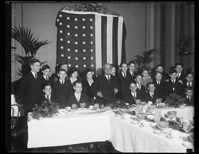 [Vice-president entertains pages. One of the yuletide events the pages of the Senate look forward to with anticipation is the annual dinner given for them by Vice-President Charles Curtis. The photograph shows the pages at this year's party, with their genial host about to carve the turkey]