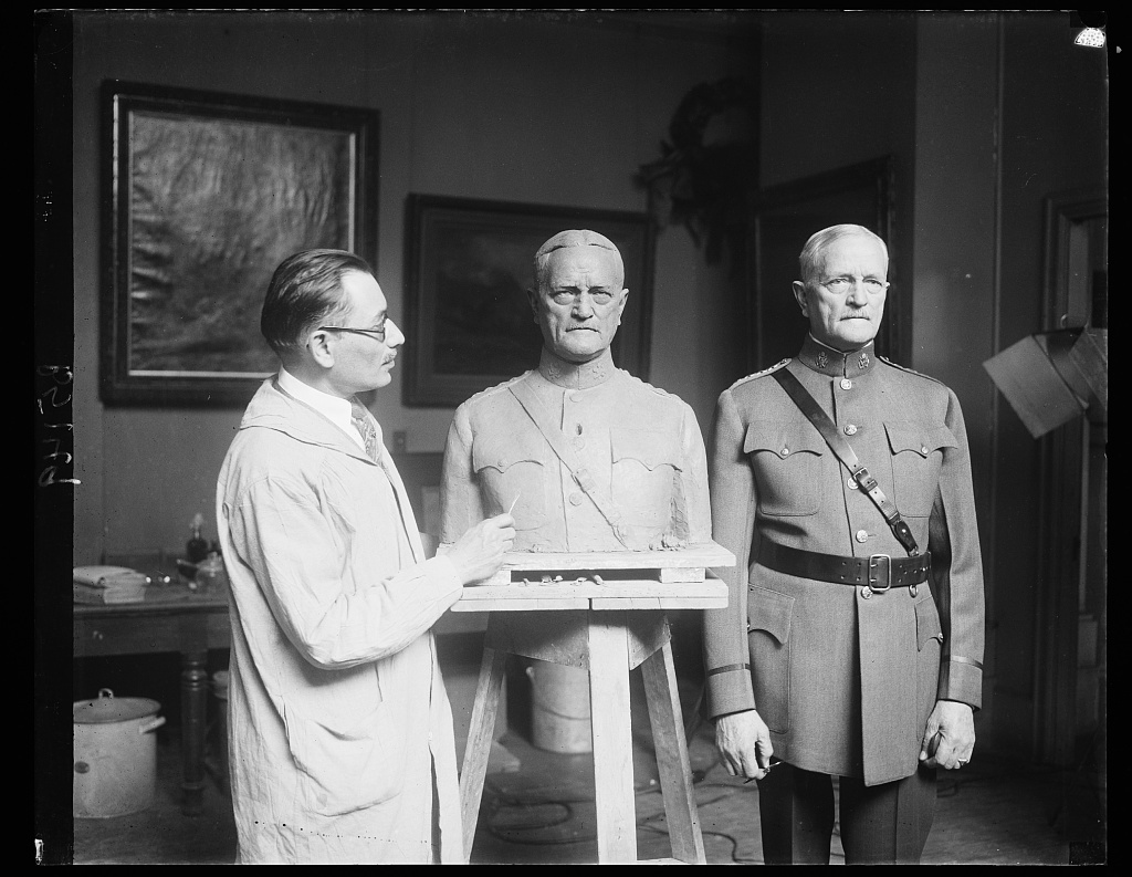 A.E.F. Commander is sculptured. General John J. Pershing, Commander of the American Expeditionary Forces in France during the World War, posing for the famous Russian sculptor, Moses Dykaar, at his studio in Washington today. 4/19/32