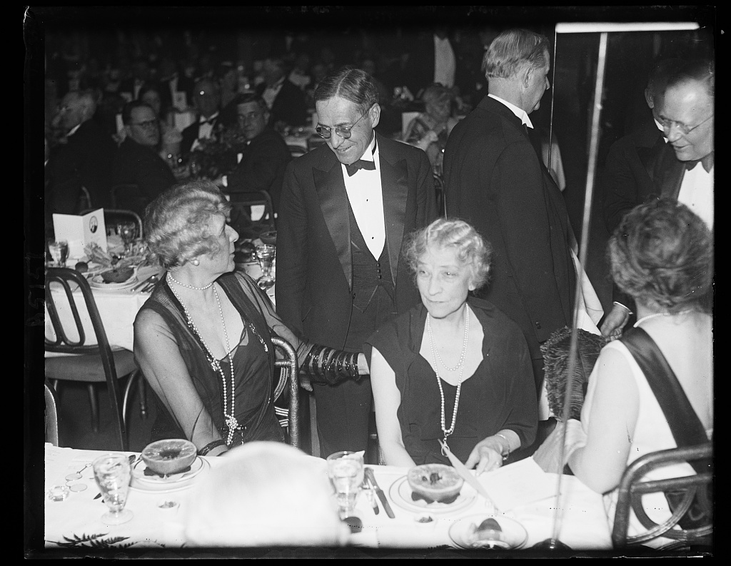 At Jefferson Day dinner. Newton D. Baker, Secretary of War during the Wilson administration and a Democratic presidential nominee this year, stops to chat with Mrs. J. Borden Harriman, (left) and Mrs. Hugh Wallace, wife of former American Ambassador to France, at the Democratic Jefferson Day Dinnerat the Willard Hotel in Washington. 4/13/32