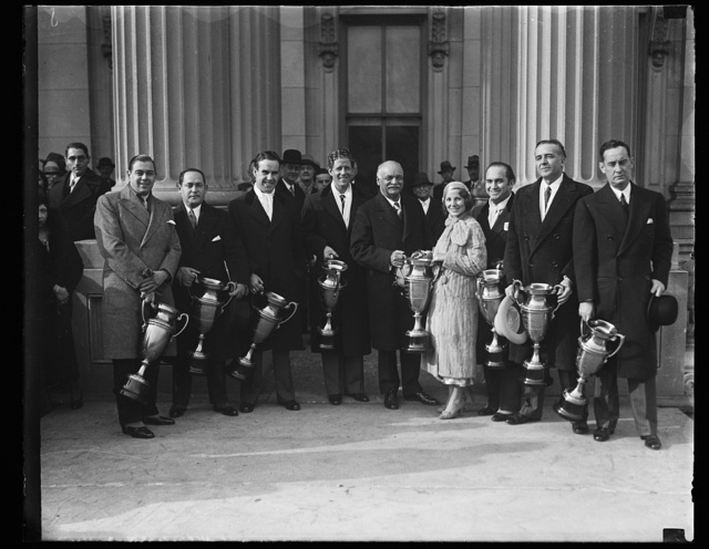 [Charles Curtis and group holding trophy cups]