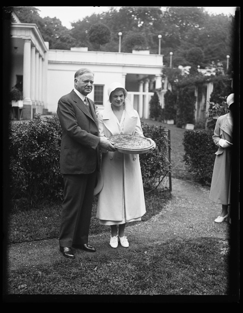 [Herbert Hoover and woman with large pie outside White House, Washington, D.C.]