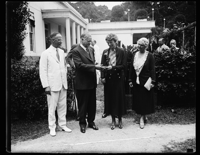 [Herbert Hoover presenting the National Geographic Society medal to Amelia Earhart; with Dr. Gilbert Grosvenor, at left. White House, Washington, D.C.]